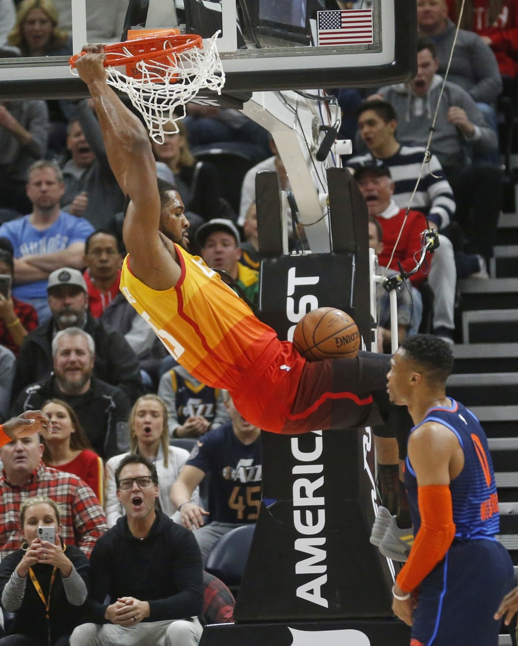 Utah Jazz forward Derrick Favors (15) dunks the ball as Oklahoma City Thunder guard Russell Westbrook (0) looks on in the first half of an NBA basketb...