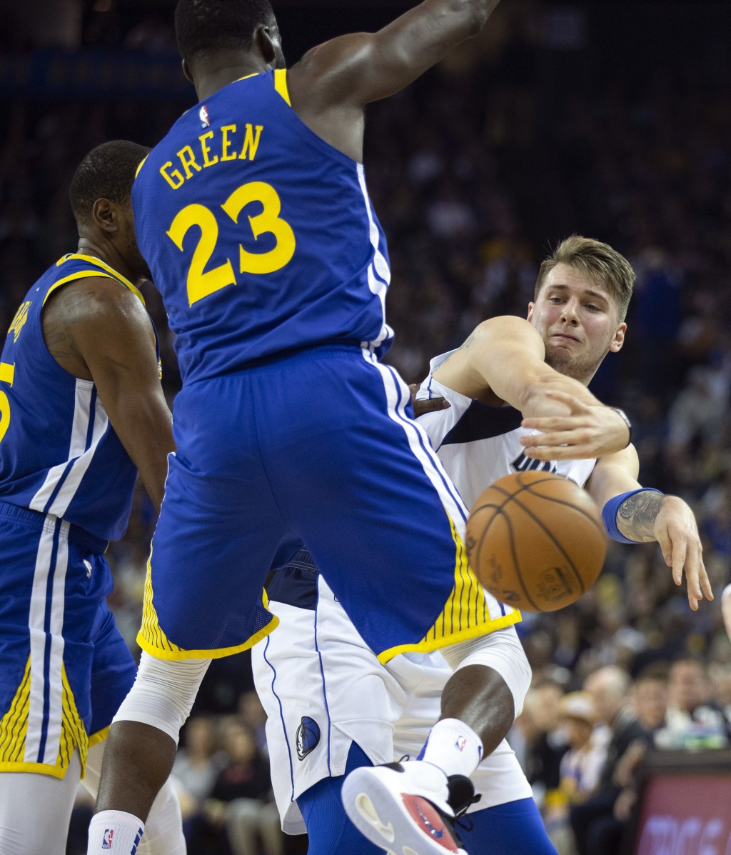 Dallas Mavericks' Luka Doncic, right, passes the ball around Golden State Warriors defenders Kevin Durant (35) and Draymond Green (23) during the seco