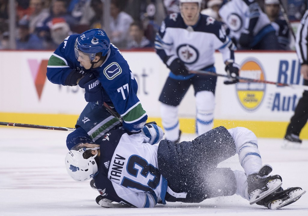 Winnipeg Jets left wing Brandon Tanev (13) fights for control of the puck with Vancouver Canucks right wing Nikolay Goldobin (77) during first-period ...