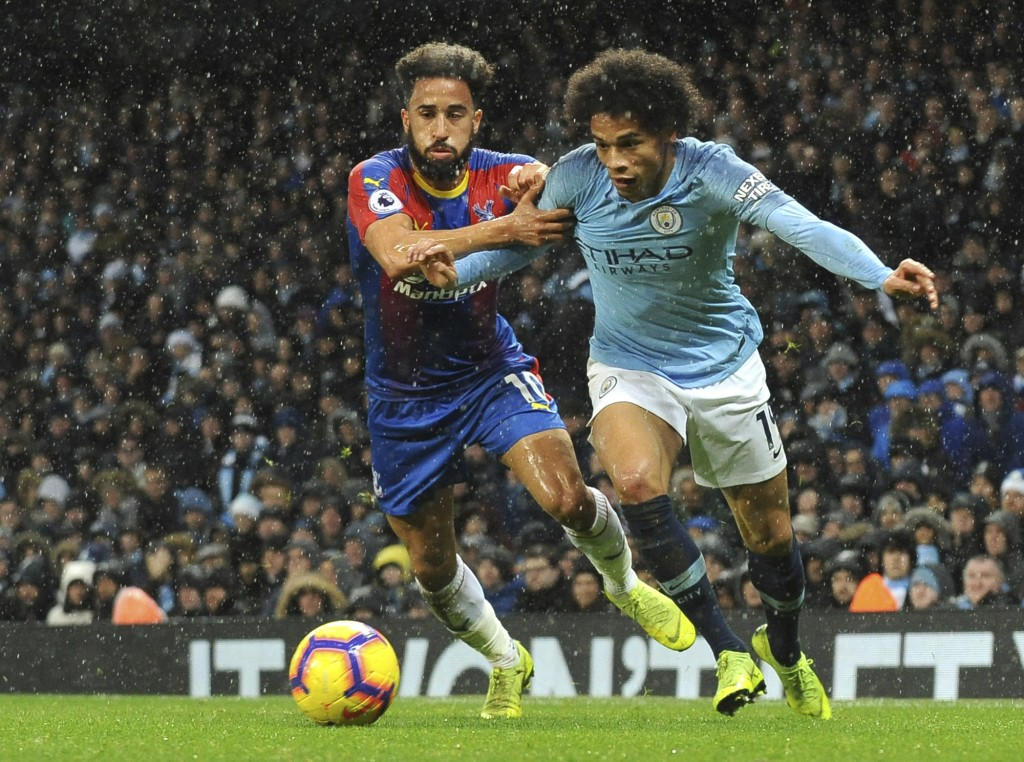 Crystal Palace's Andros Townsend, left, and Manchester City's Leroy Sane challenge for the ball during the English Premier League soccer match between...