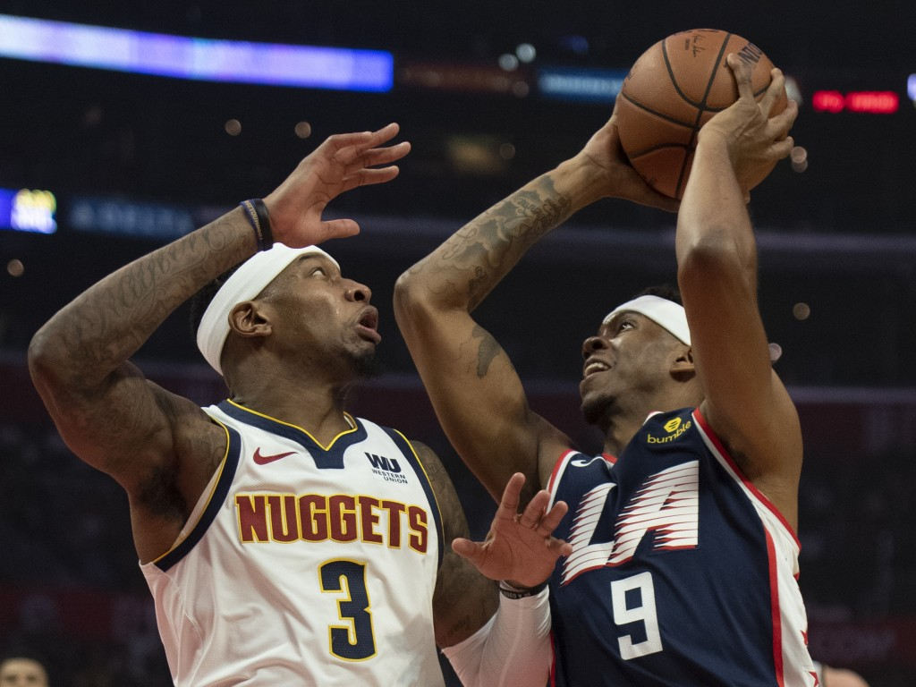 Los Angeles Clippers guard Tyrone Wallace, right, goes up to the basket under pressure as Denver Nuggets forward Torrey Craig defends him during the f