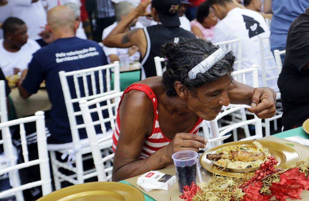 A homeless person eats during a Christmas lunch served to homeless people by the non-governmental organization SP Invisivel in downtown Sao Paulo, Bra