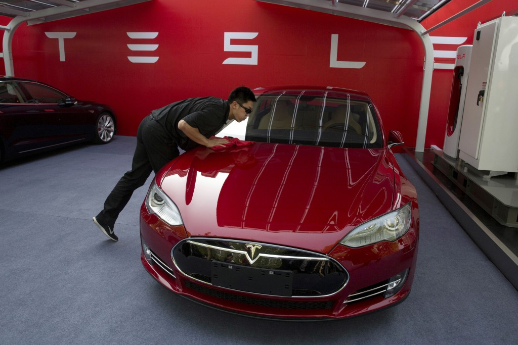 FILE - In this April 22, 2014, file photo, a worker cleans a Tesla Model S sedan before an event to deliver the first set of cars to customers in Beij
