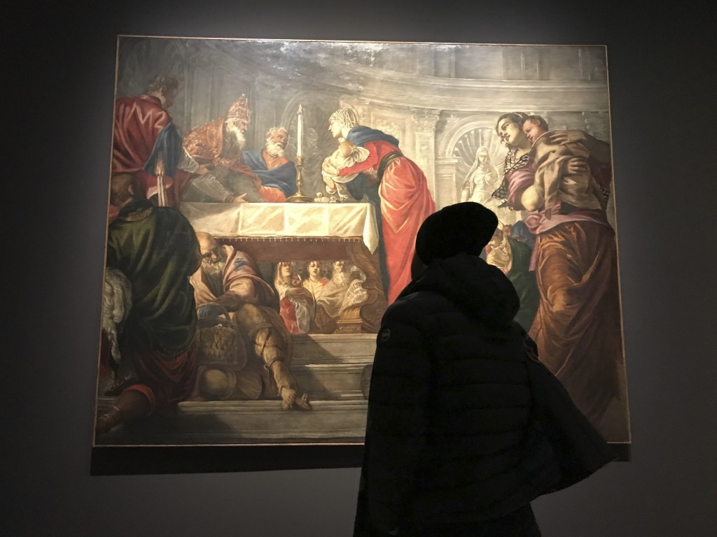"""In this Dec. 3, 2018 photo, a visitor to an exhibition of Tintoretto works looks at his """"Presentation of Jesus in the Temple"""" at the Ducal Palace in V..."""