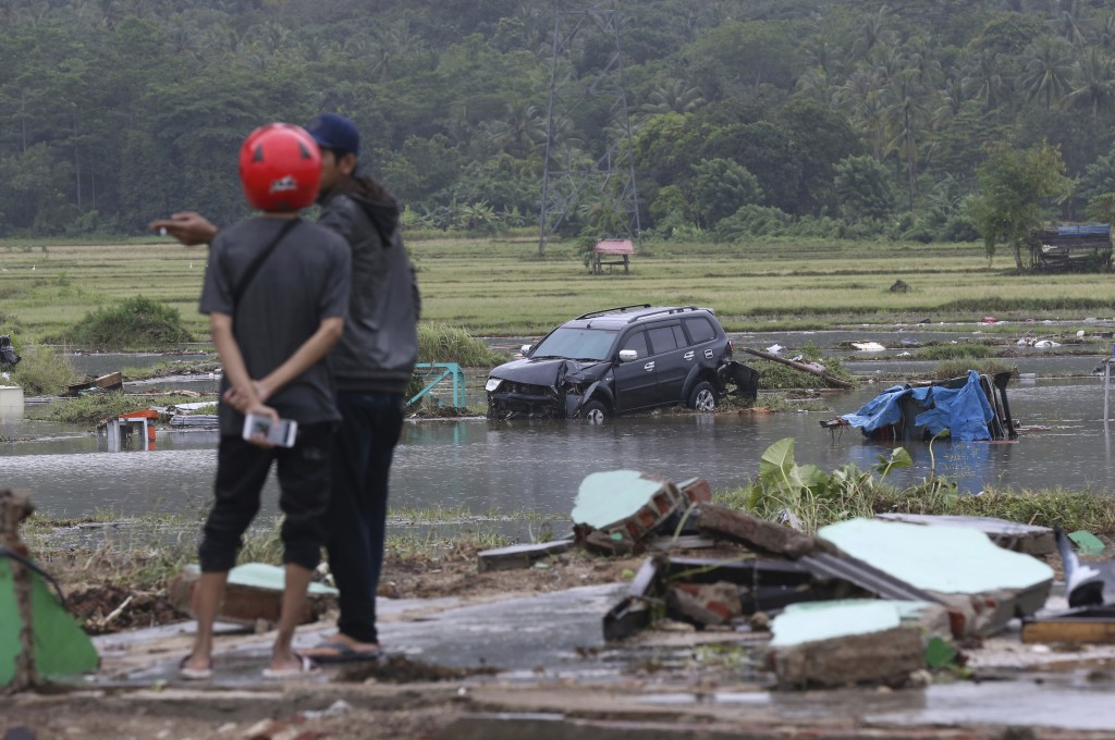 Villagers stand near a car damaged by a tsunami in Carita, Indonesia, Sunday, Dec. 23, 2018. The tsunami occurred after the eruption of a volcano arou...