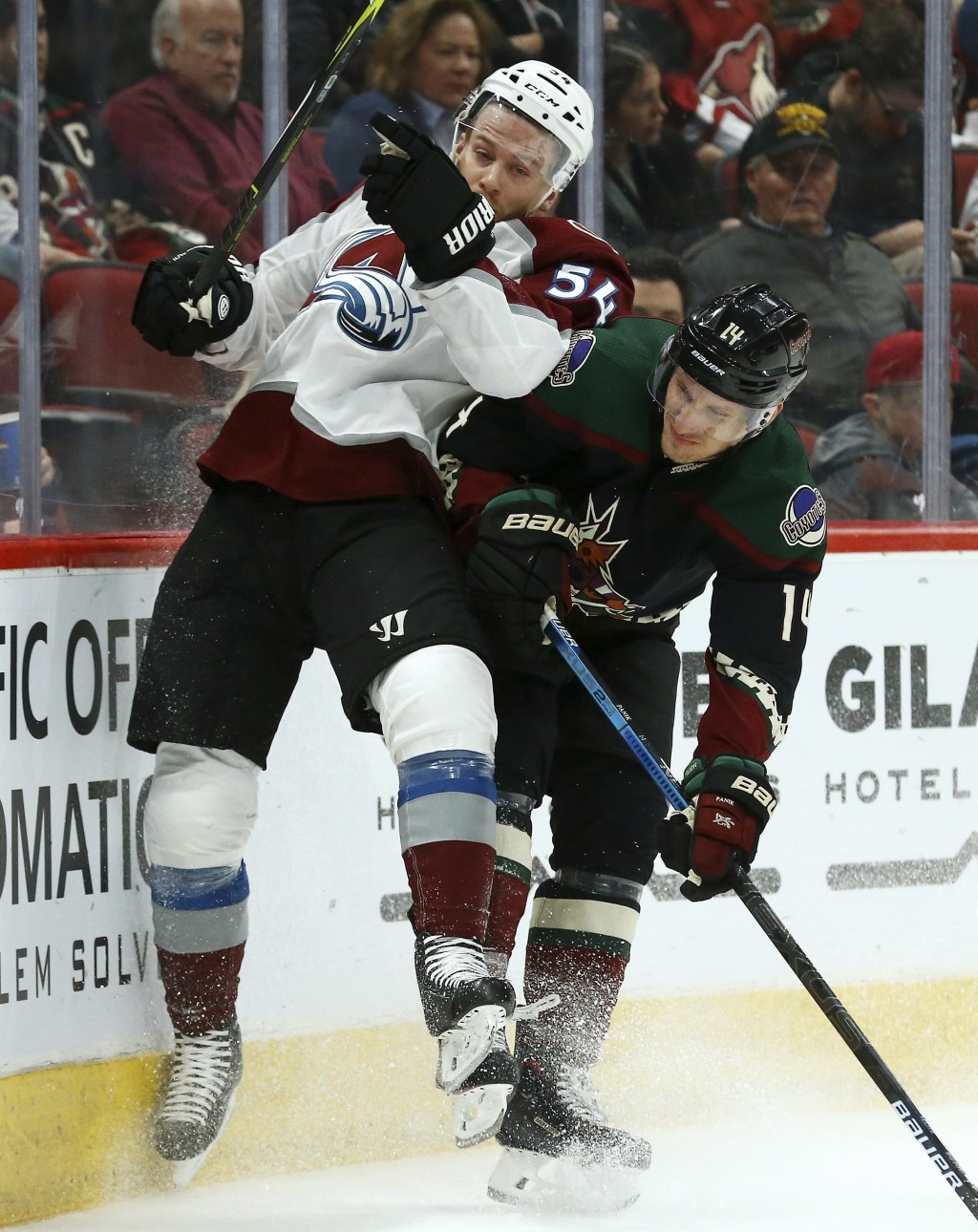 Arizona Coyotes right wing Richard Panik (14) checks Colorado Avalanche defenseman Anton Lindholm (54) into the boards during the second period of an ...