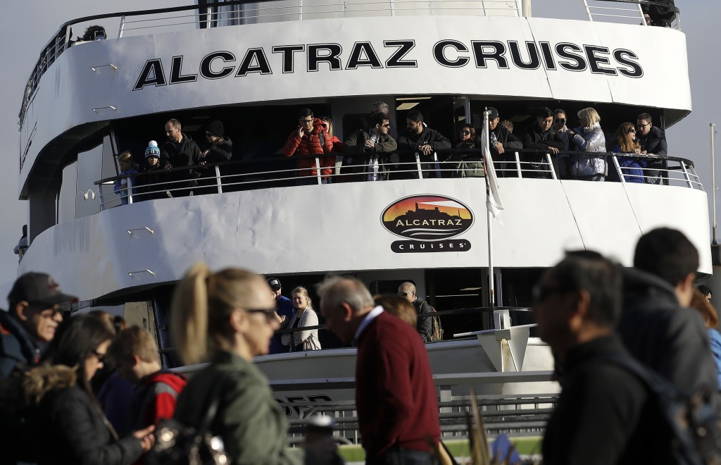 An Alcatraz Cruise ship waits to depart as customers stand in line for ferry service in San Francisco, Saturday, Dec. 22, 2018. A partial federal shut...