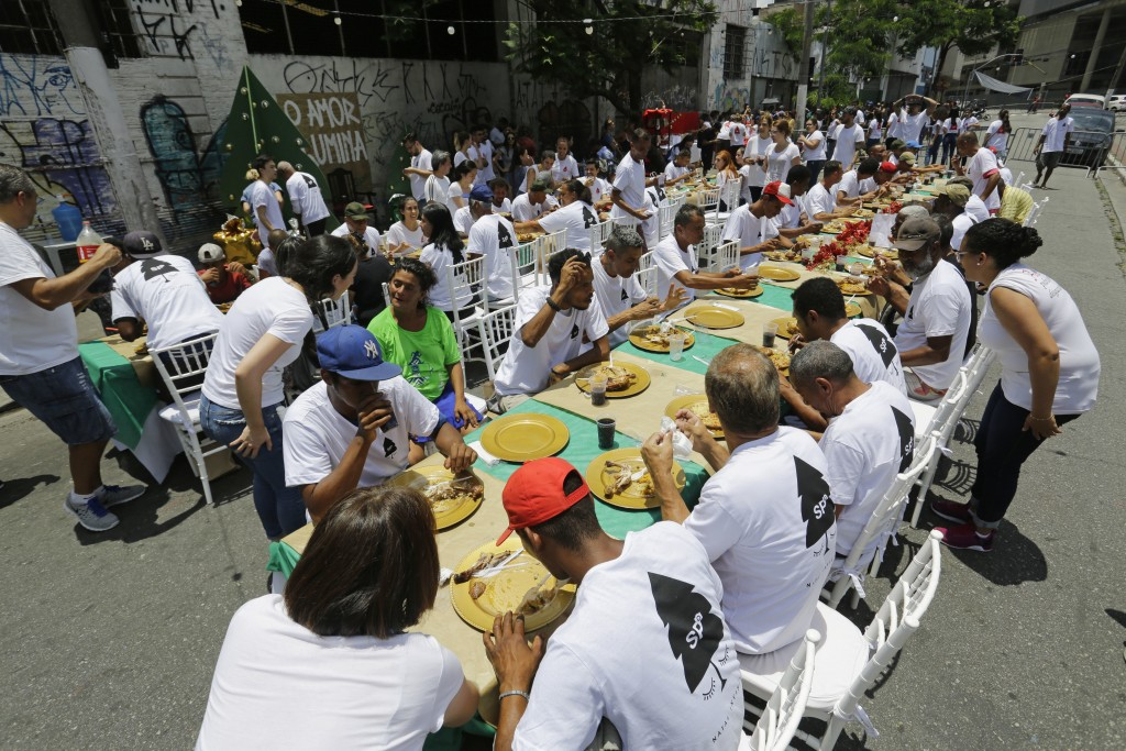 People eat and drink during a Christmas lunch served to homeless people by the non-governmental organization SP Invisivel in downtown Sao Paulo, Brazi...