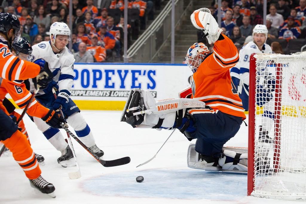Edmonton Oilers goaltender Mikko Koskinen (19) makes a save against Tampa Bay Lightning defenseman Mikhail Sergachev (98) during the first period of a...