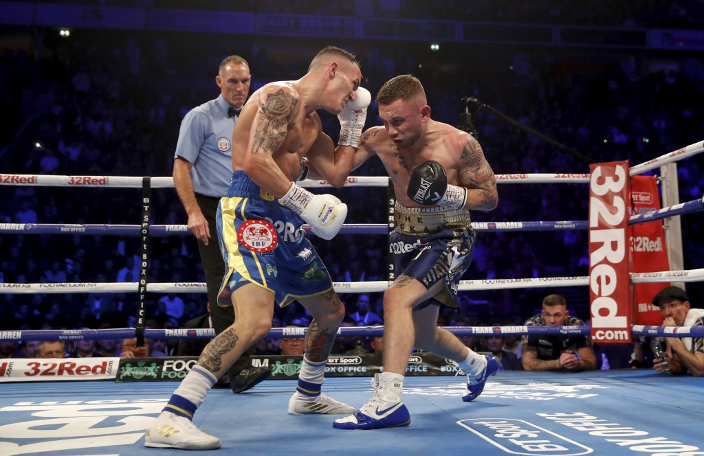 Josh Warrington, left, is hit by Carl Frampton during the IBF featherweight title boxing bout Saturday, Dec. 22, 2018, in Manchester, England. (Martin