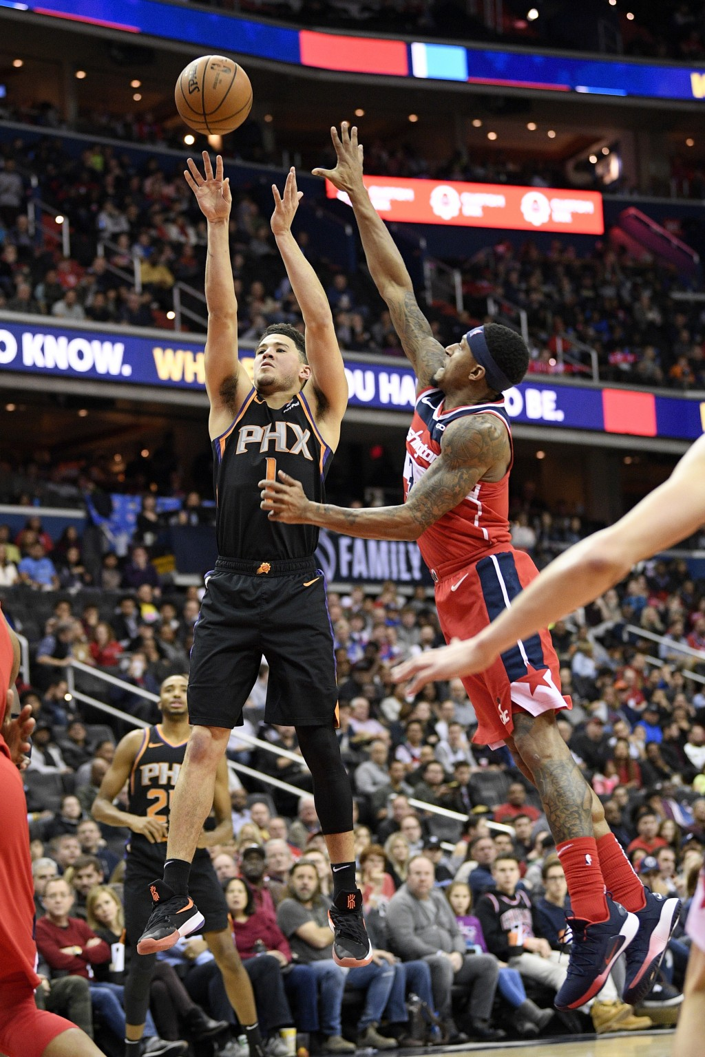 Phoenix Suns guard Devin Booker (1) shoots against Washington Wizards guard Bradley Beal (3) during the first half of an NBA basketball game, Saturday...
