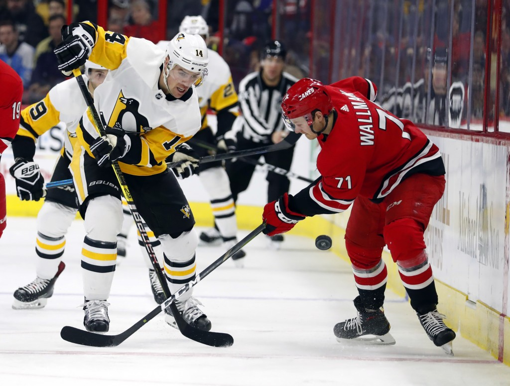 Pittsburgh Penguins' Tanner Pearson (14) wins the battle with Lucas Wallmark (71) during the second period of an NHL hockey game, Saturday, Dec. 22, 2
