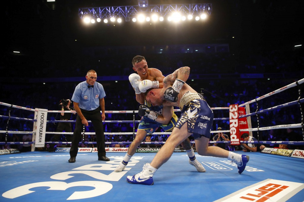 Carl Frampton, right, tries to avoid a punch from Josh Warrington during their IBF featherweight title boxing bout Saturday, Dec. 22, 2018, in Manches