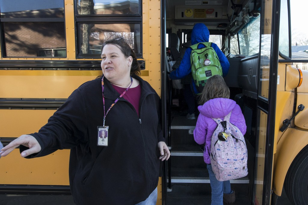 In this Dec. 20, 2018 photo, Kristi Meyers, Lincoln Public Schools bus driver, loads children onto her bus, in Lincoln, Neb. School districts througho...