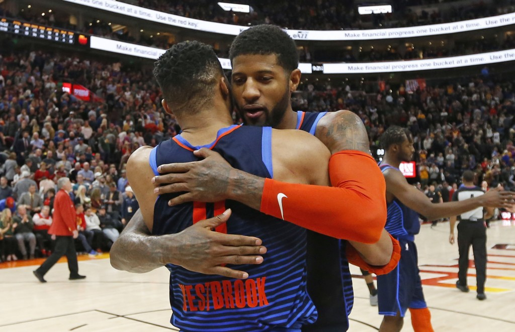 Oklahoma City Thunder Paul George, rear, and Russell Westbrook (0) hug following their NBA basketball game against the Utah Jazz Saturday Dec. 22, 201...