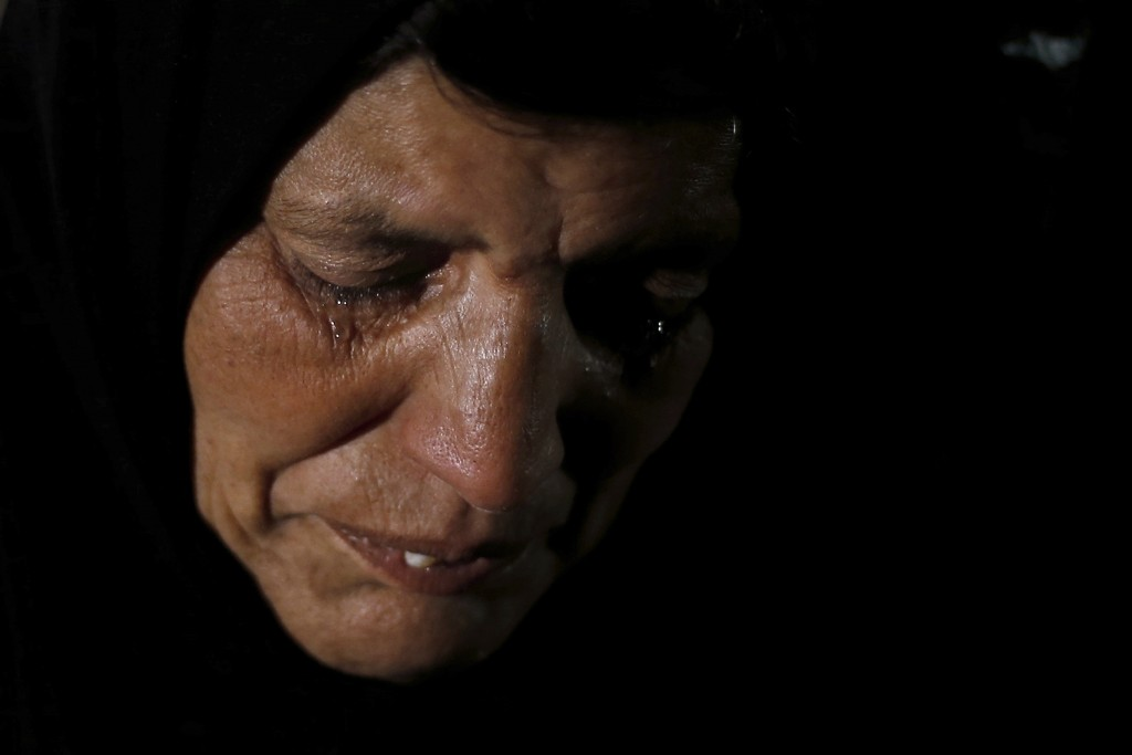 In this Tuesday, Dec. 18, 2018, photo, Syrian refugee Itihad Sayed weeps during an interview with The Associated Press at her home in Ouzai refugee co...