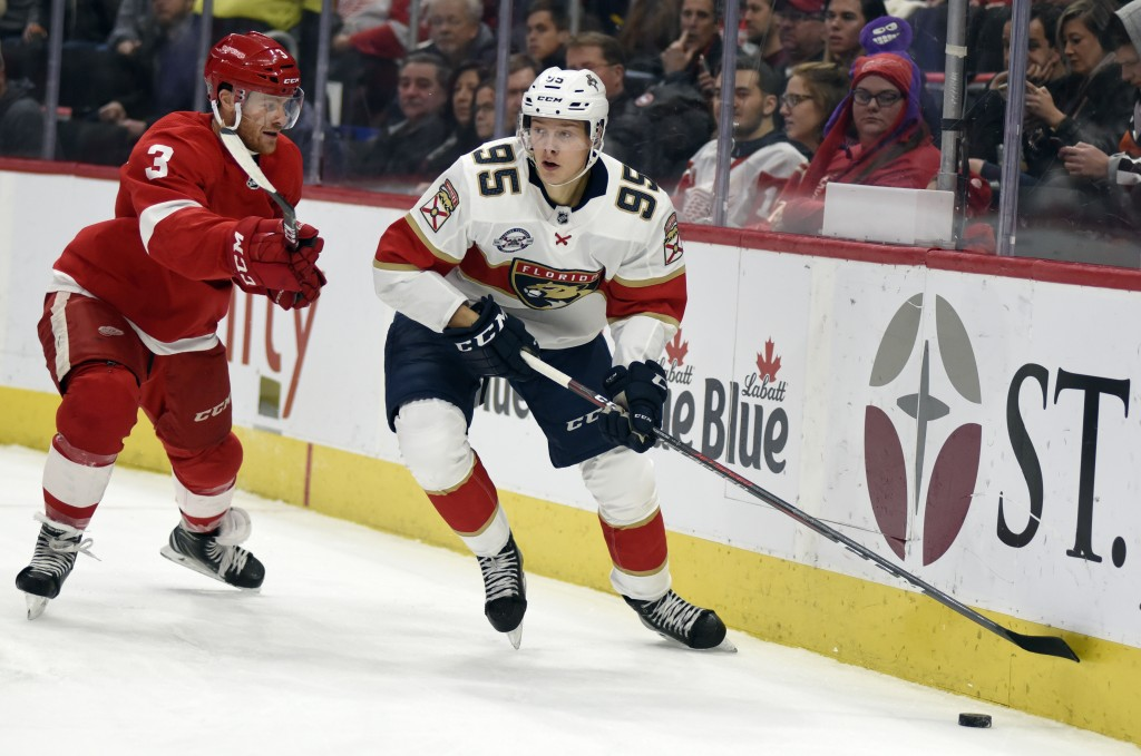 Florida Panthers center Henrik Borgstrom (95) of Finland keeps the puck away from Detroit Red Wings defenseman Nick Jensen (3) during the first period...