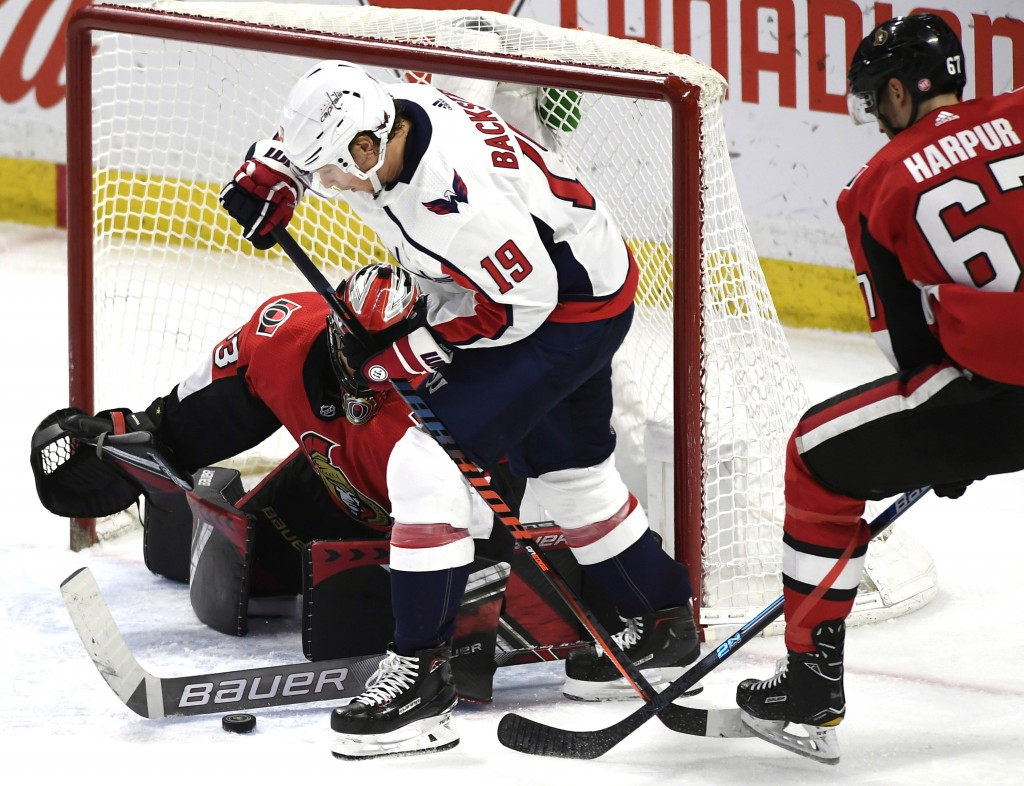 Ottawa Senators goaltender Mike McKenna (33) uses his stick to control the puck in the crease as defenseman Ben Harpur (67) tries to force back the st...
