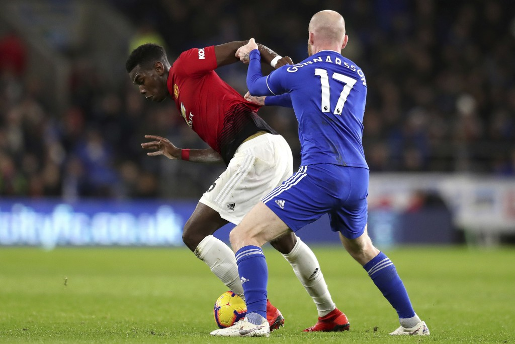Manchester United midfielder Paul Pogba, left, fights for the ball with Cardiff City midfielder Aron Gunnarsson during the English Premier League matc...