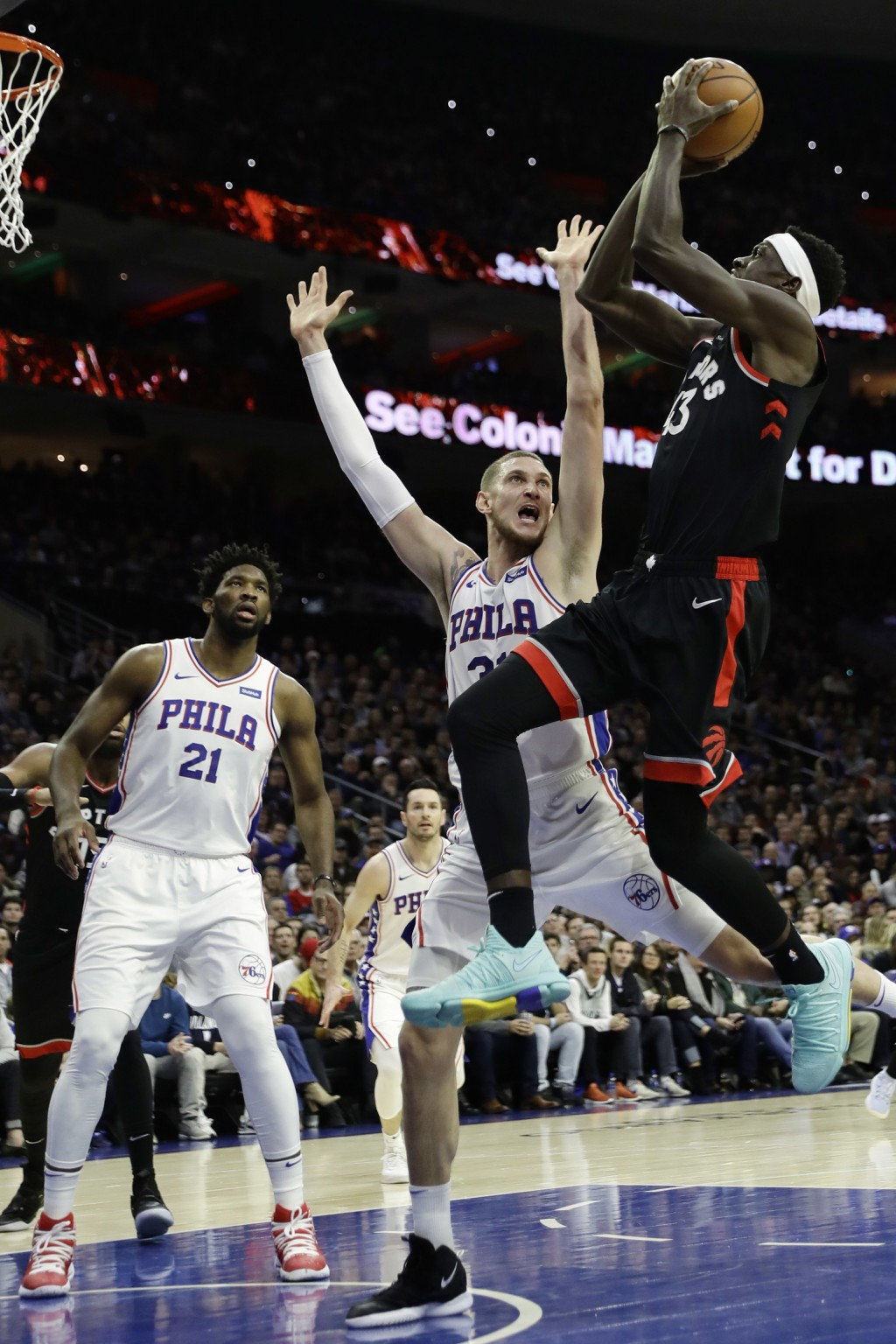 Toronto Raptors' Pascal Siakam, right, goes up for a shot against Philadelphia 76ers' Mike Muscala during the first half of an NBA basketball game, Sa...