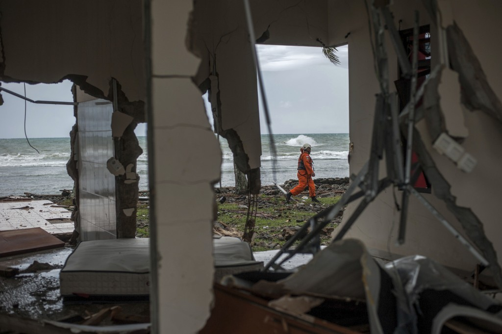 In this Sunday, Dec. 23, 2018, photo, a rescuer is seen through a damaged house as he takes part in a search operation of tsunami victims in Carita, I...