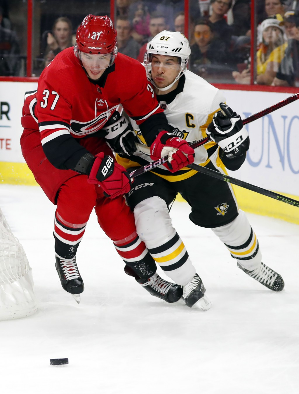Carolina Hurricanes' Andrei Svechnikov (37) battles with Pittsburgh Penguins' Sidney Crosby (87) behind the net during the first period of an NHL hock