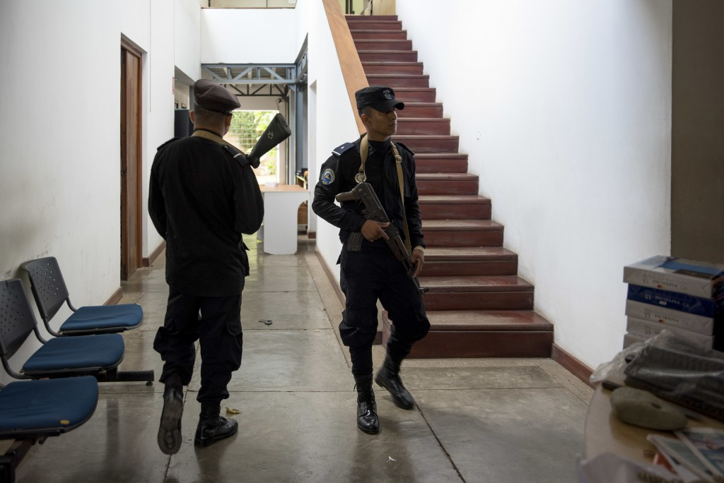 """In this Dec. 14, 2018 photo, National Police officers walk inside office of the independent media outlet Confidencial, in Managua, Nicaragua. """"All Nic"""