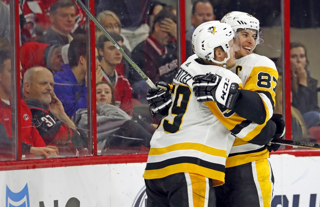 Pittsburgh Penguins' Jake Guentzel (59) is congratulated on his goal by teammate Sidney Crosby (87) during the second period of an NHL hockey game aga...