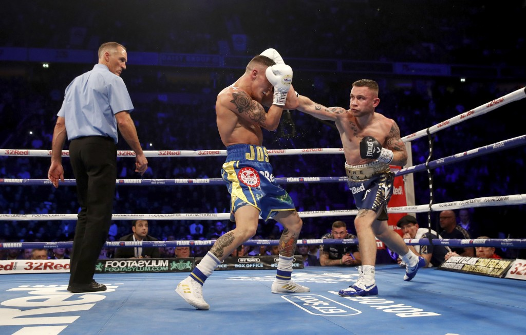 Carl Frampton, right, throws a right to Josh Warrington during their IBF featherweight title boxing bout Saturday, Dec. 22, 2018, in Manchester, Engla...