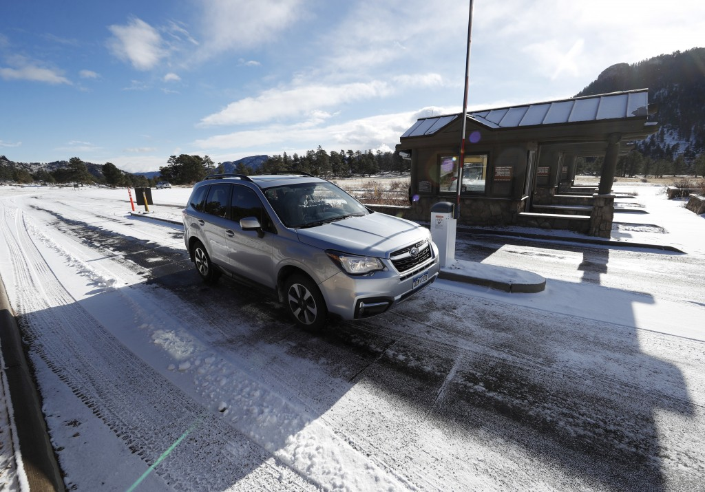 Motorists glide through the unattended toll booths at Rocky Mountain National Park Saturday, Dec. 22, 2018, in Estes Park, Colo. A partial federal shu...