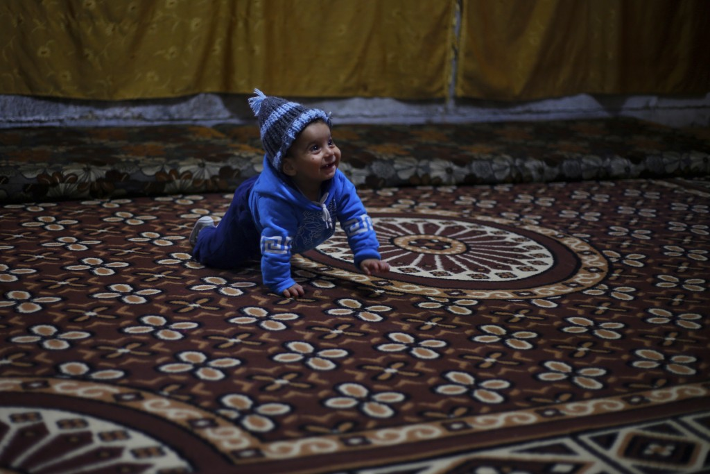 In this Tuesday, Dec. 18, 2018, photo, Syrian refugee Bashar Qarqour crawls inside his family home in Ouzai refugee compound, in the southern port cit...