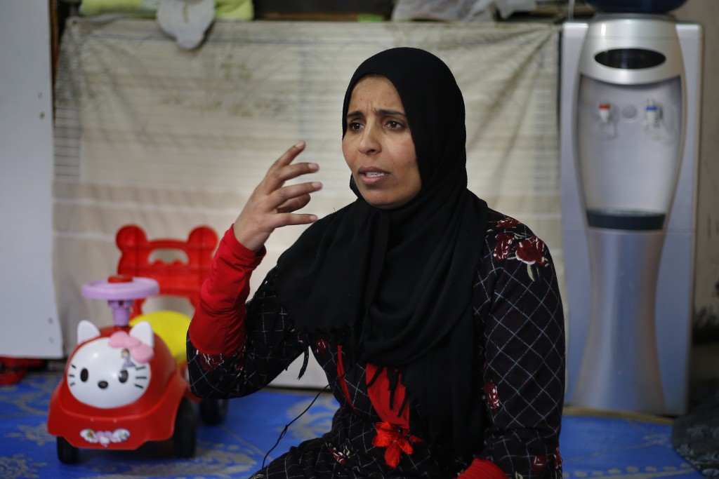 In this Tuesday, Dec. 18, 2018, photo, Syrian refugee Rozan Qarqour speaks during an interview with The Associated Press at her home in Ouzai refugee ...