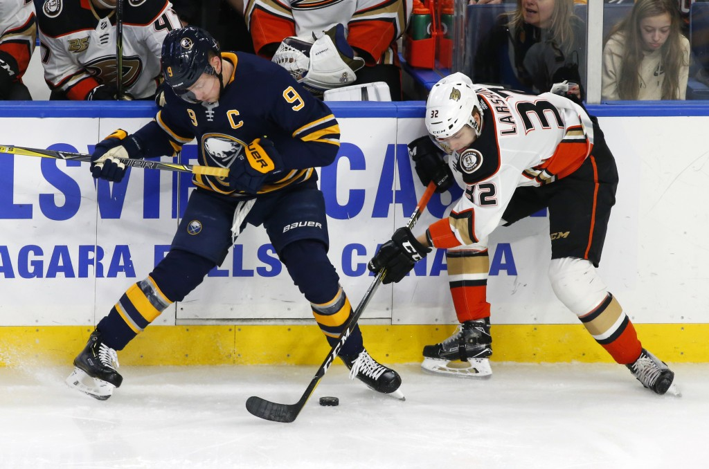 Buffalo Sabres forward Jack Eichel (9) and Anaheim Ducks defenseman Jacob Larsson (32) battle along the boards during the first period of an NHL hocke...