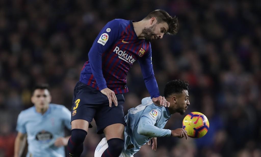 FC Barcelona's Gerard Pique, left, heads for the ball with Celta Vigo's Sofiane Boufal during the Spanish La Liga soccer match between FC Barcelona an...