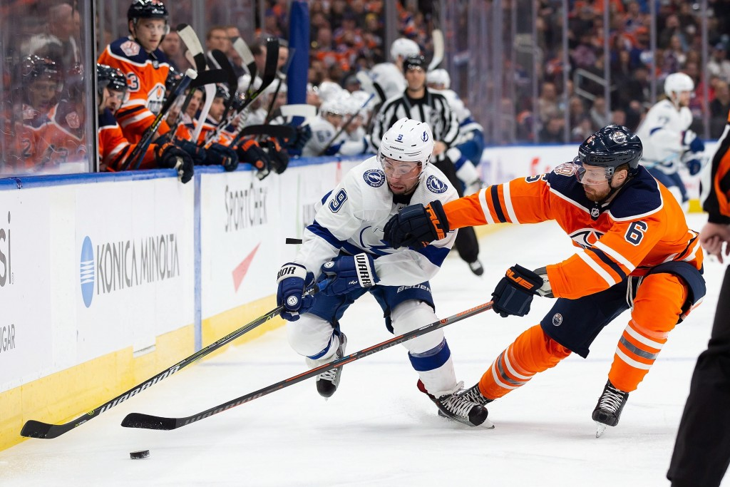 Edmonton Oilers defenseman Adam Larsson, right, competes for the puck Tampa Bay Lightning center Tyler Johnson during the first period of an NHL hocke...