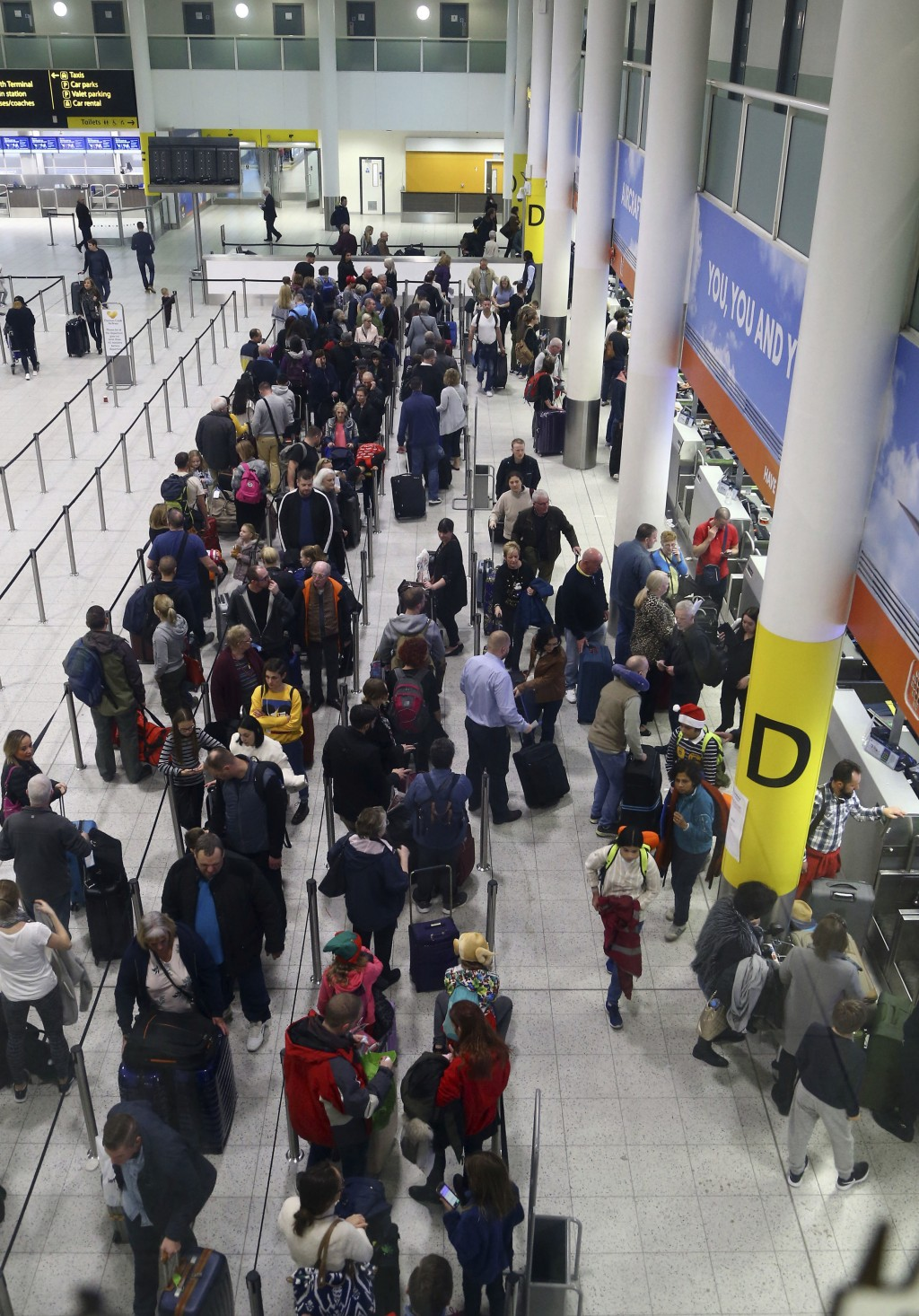 Passengers queue for flights at Gatwick Airport as the airport and airlines work to clear the backlog of flights delayed by a drone incident earlier i...