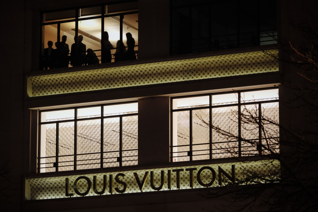 Employees of the brand Louis Vuitton watch a Yellow Vests demonstration on the Champs Elysees Avenue in Paris Saturday, Dec. 22, 2018. France's yellow