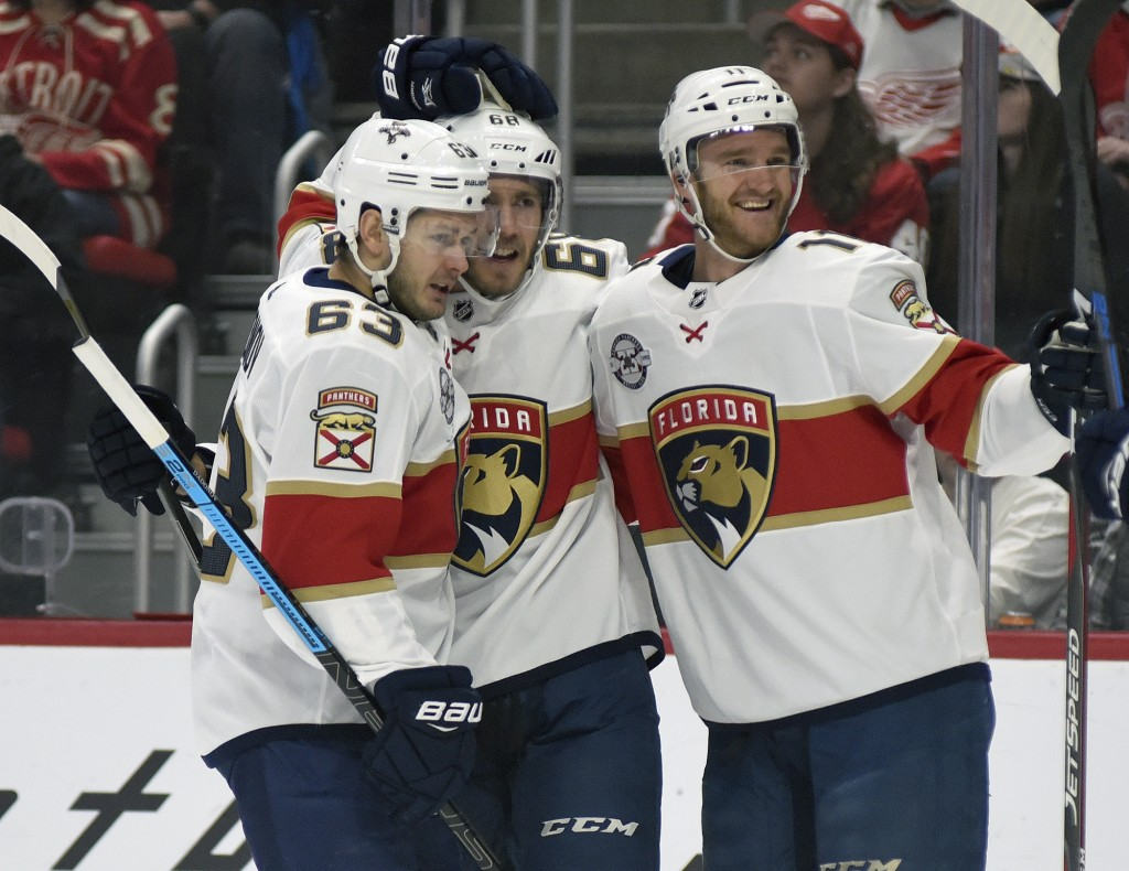 Florida Panthers' Mike Hoffman (68), center, is congratulated by right wing Evgenii Dadonov (63) of Russia and left wing Jonathan Huberdeau (11) after