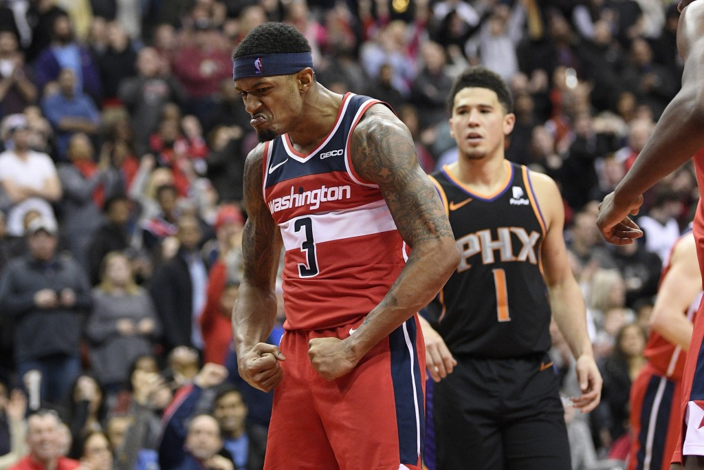 Washington Wizards guard Bradley Beal (3)  reacts after he made a basket during triple overtime of an NBA basketball game next to Phoenix Suns guard D