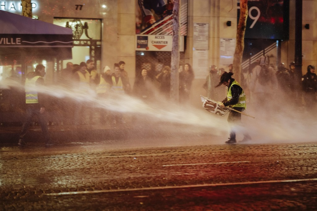 A demonstrator wearing a yellow vest is blasted with a police water canon on the Champs Elysees avenue in Paris Saturday, Dec. 22, 2018. France's yell