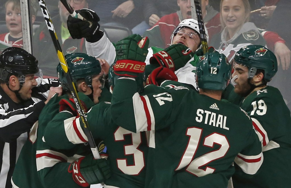 Minnesota Wild players converge against Dallas Stars' Valeri Nichushkin, top center, of Russia as a linesman, left, tries to break up a melee in the f...