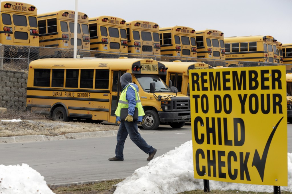 In this Dec. 20, 2018 photo, a driver walks away from the school bus parking lot after his morning shift, in Omaha, Neb. School districts throughout t...