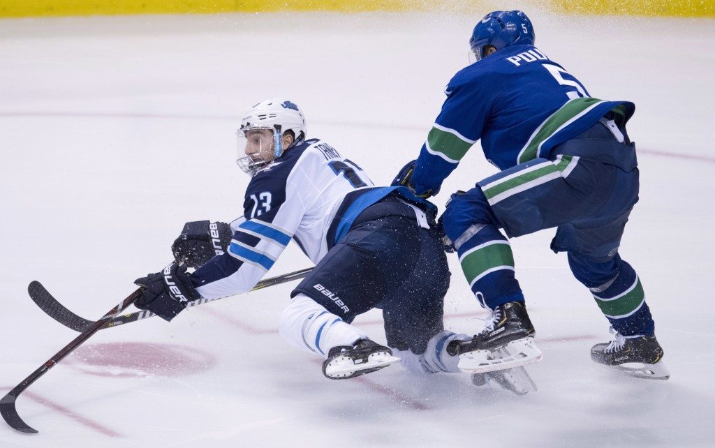 Winnipeg Jets left wing Brandon Tanev (13) fights for control of the puck with Vancouver Canucks defenseman Derrick Pouliot (5) during the third perio...
