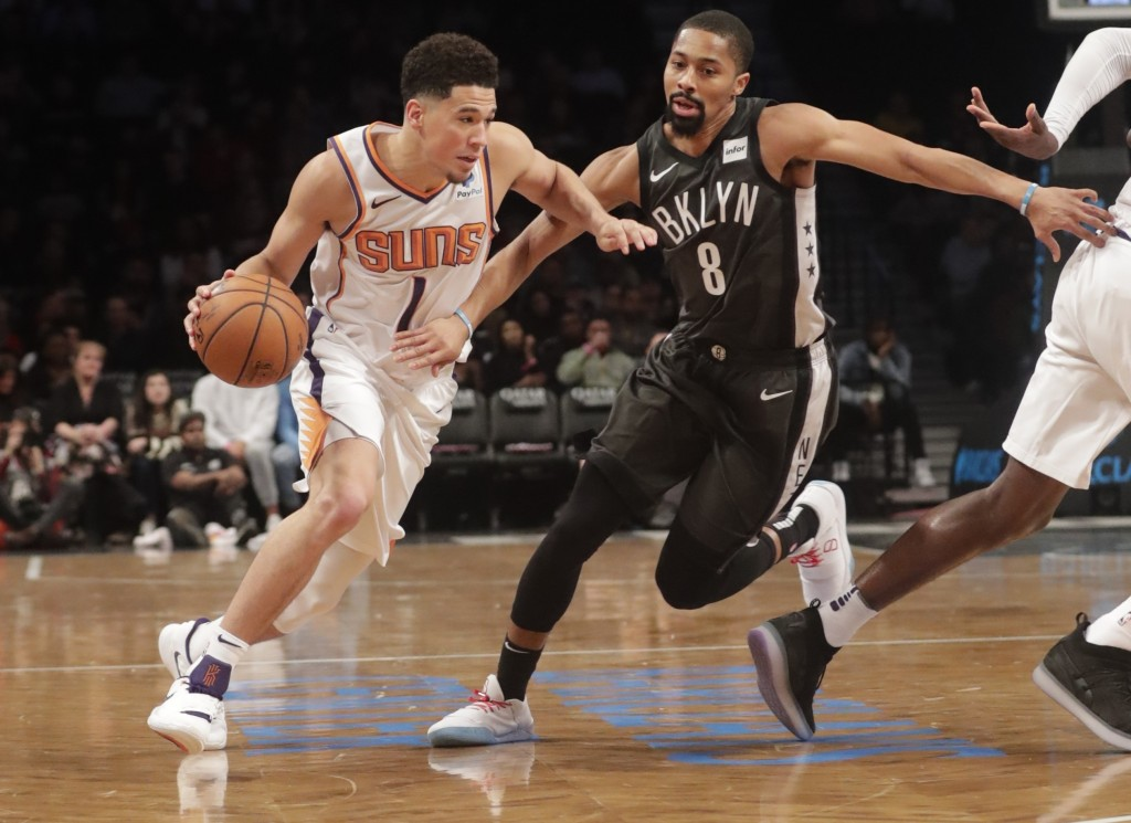 Brooklyn Nets' Spencer Dinwiddie (8) defends against Phoenix Suns' Devin Booker (1) during the first half of an NBA basketball game Sunday, Dec. 23, 2...