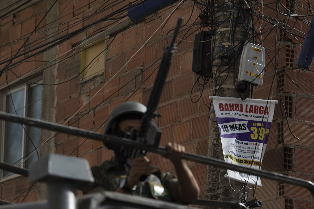 In this May. 19, 2018 photo, a soldier patrols where an add offers internet service in the Bateau Mouche slum of Rio de Janeiro, Brazil. Militias impo...
