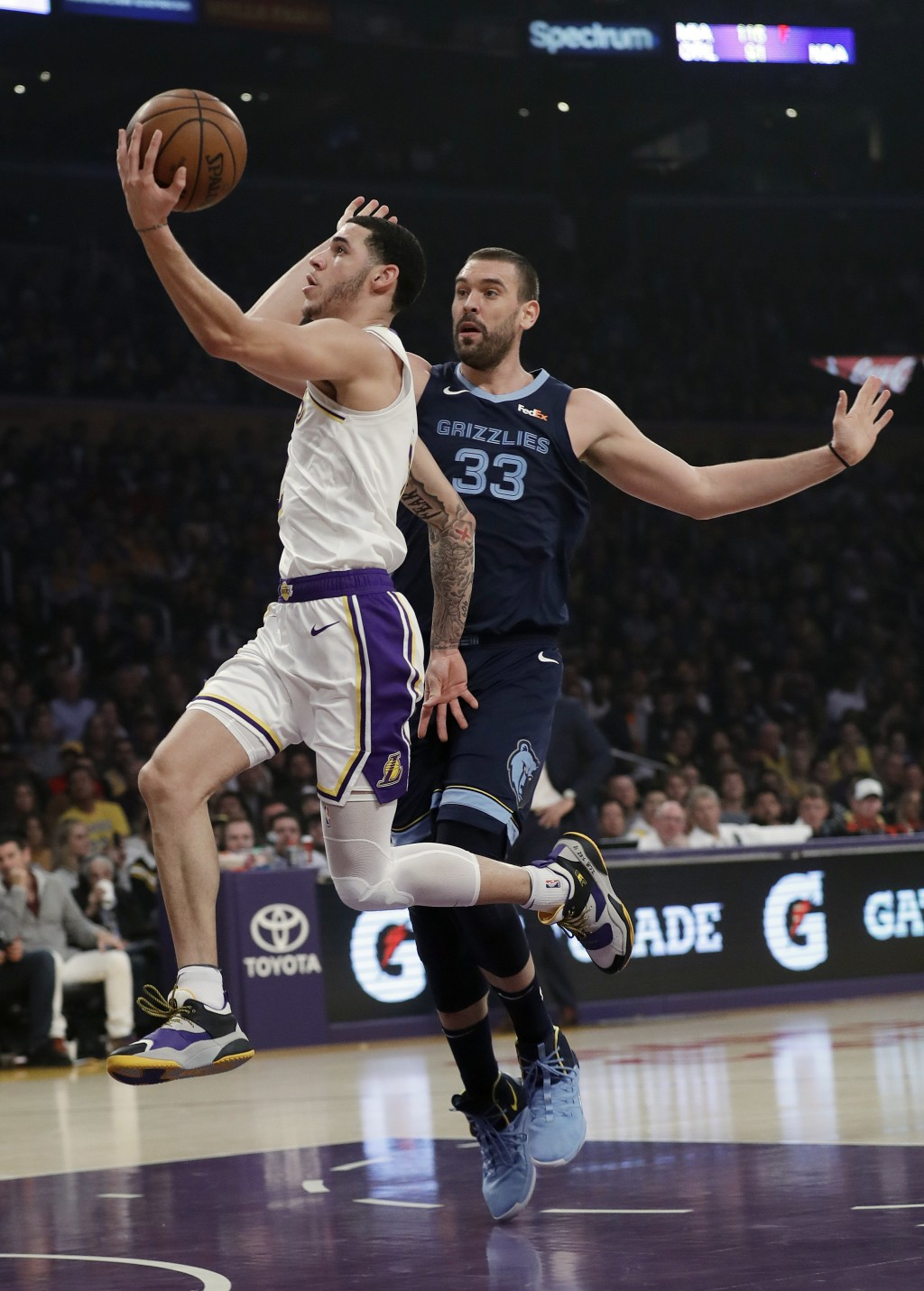 Los Angeles Lakers' Lonzo Ball, left, drives past Memphis Grizzlies' Marc Gasol (33) during the first half of an NBA basketball game Sunday, Dec. 23, ...