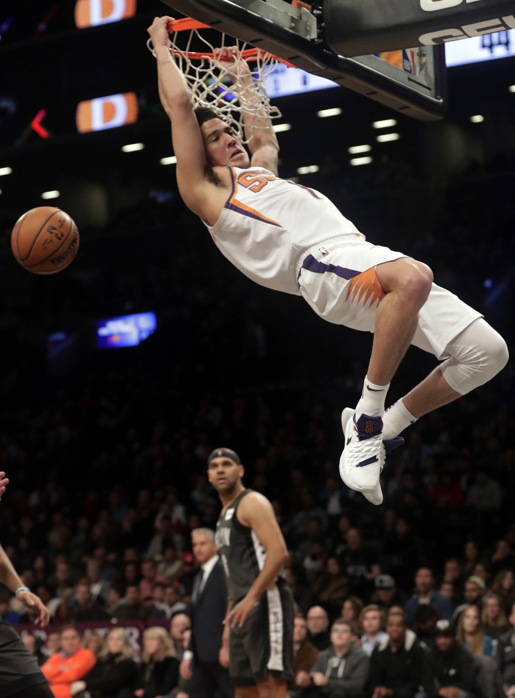 Phoenix Suns' Devin Booker (1) dunks in front of Brooklyn Nets' Jared Dudley during the first half of an NBA basketball game Sunday, Dec. 23, 2018, in...