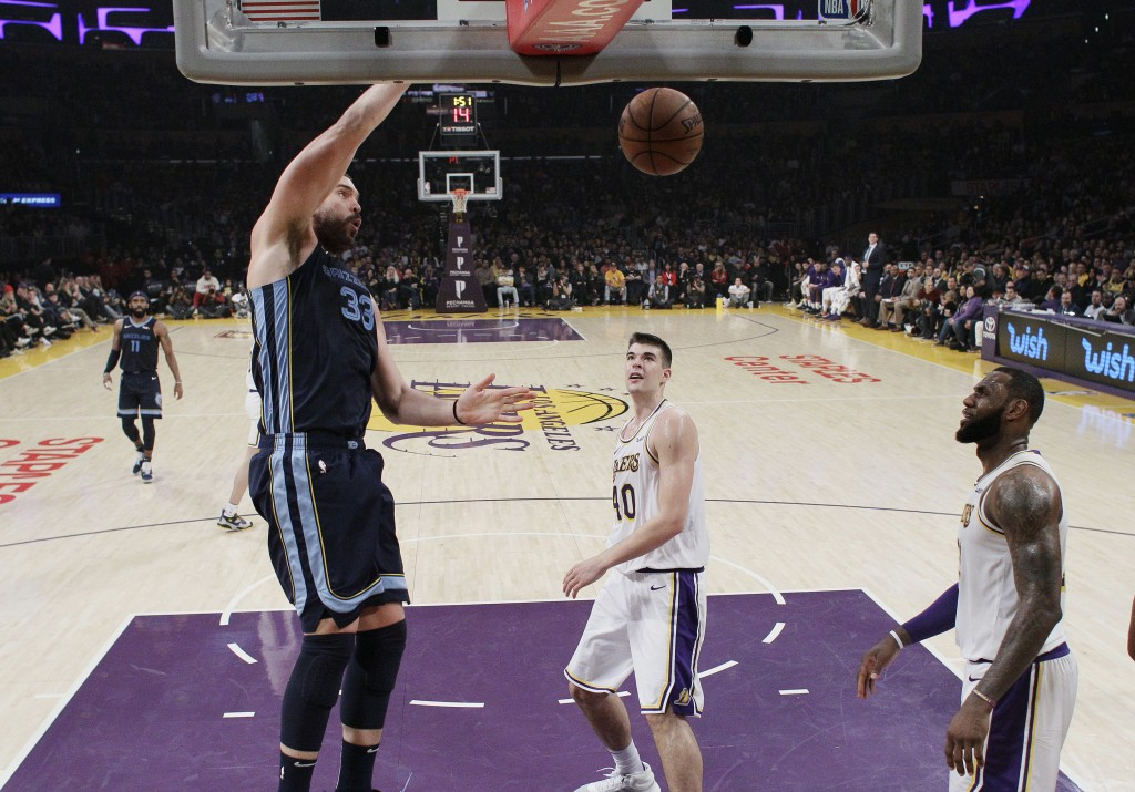 Memphis Grizzlies' Marc Gasol, left, dunks next to Los Angeles Lakers' Ivica Zubac, center, and LeBron James during the first half of an NBA basketbal...