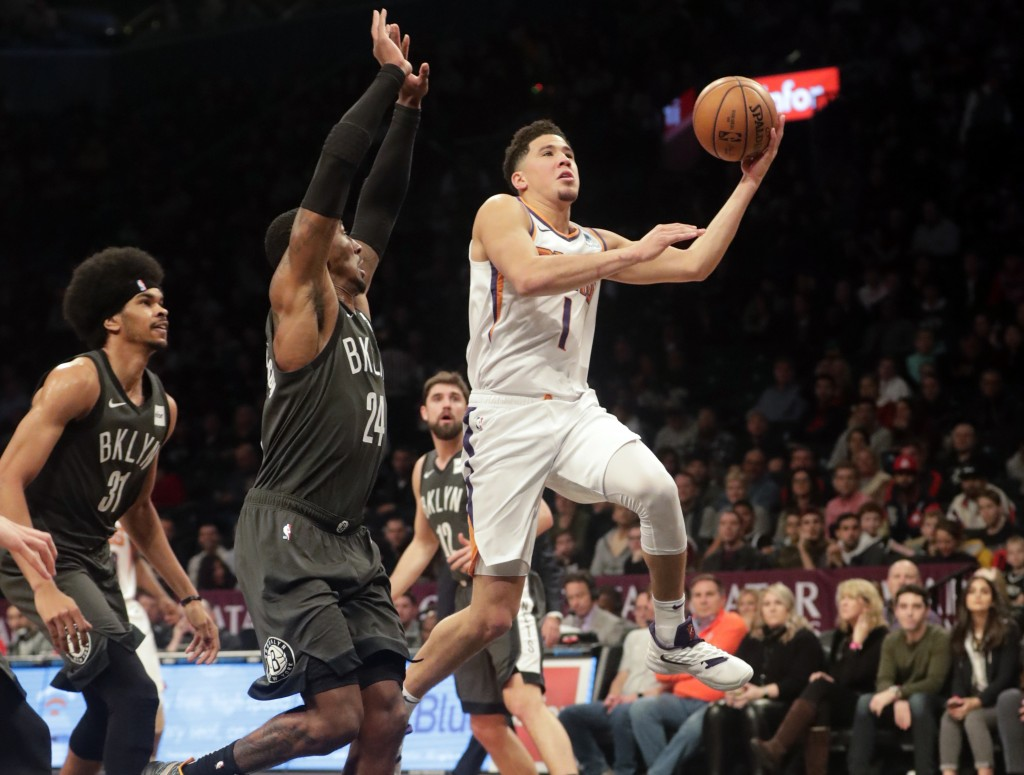 Phoenix Suns' Devin Booker (1) drives past Brooklyn Nets' Rondae Hollis-Jefferson (24) during the first half of an NBA basketball game Sunday, Dec. 23...