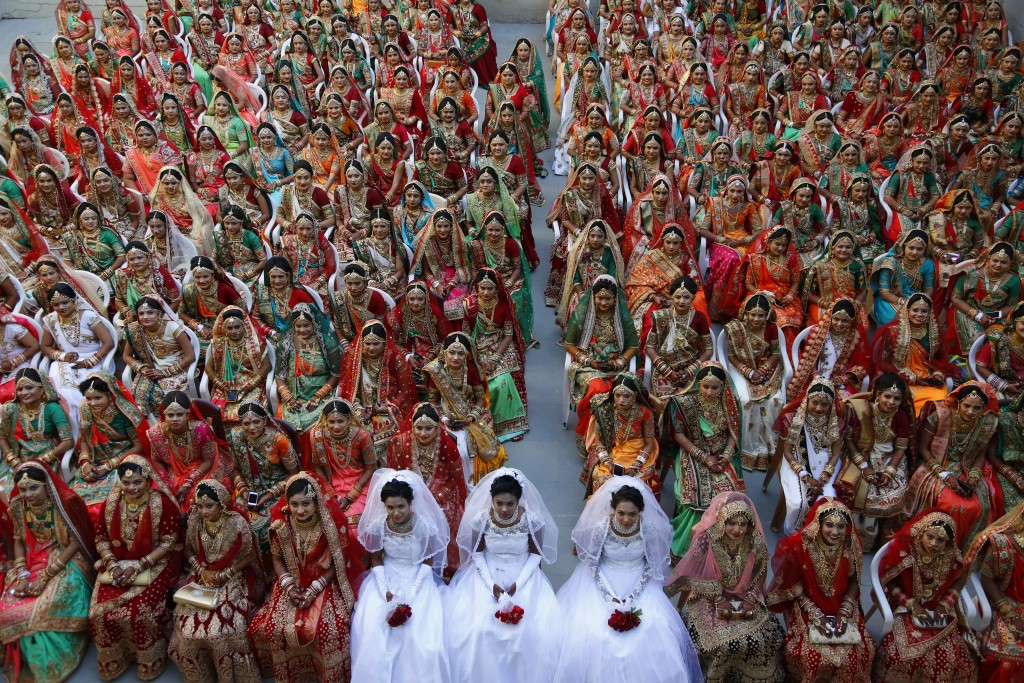 In this Sunday, Dec. 23, 2018, file photo, Indian brides sit together for a group photograph during a mass wedding in Surat, India. Two hundred and si...